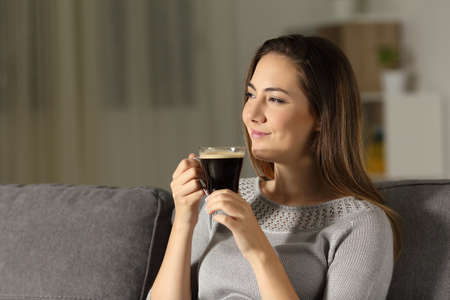 Satisfied woman enjoying coffee in the night sitting on a couch in the living room at home