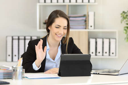 Happy office worker waving in a video conference with a tablet on a desktop