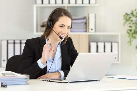 teleoperador feliz que tiene una videoconferencia con un ordenador portátil que hace con su mano en la oficina