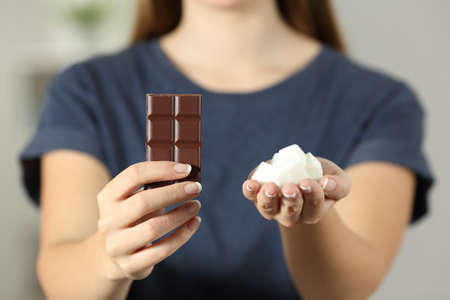 Front view close up of a woman hands showing sugar and chocolate sitting on a couch in the living room at home