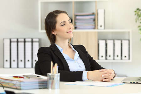 Proud office worker looking away sitting on a chair Stock Photo