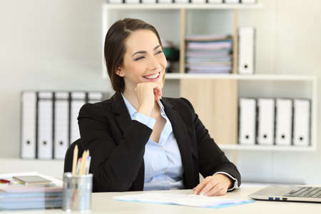 Happy office worker thinking and looking at side at workplace