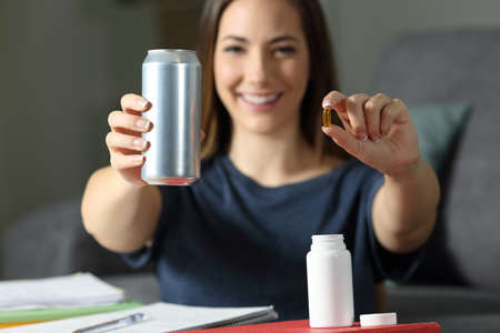 Happy student showing an energy drink tin and vitamin supplement pills at home Stock Photo