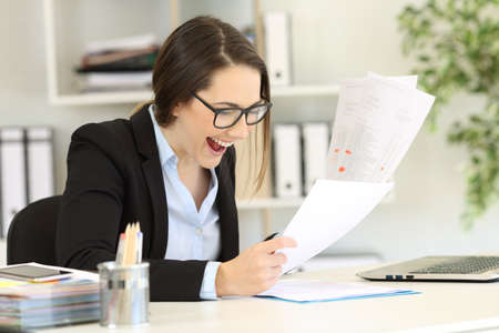 Excited office worker checking sales paper reports on a desk