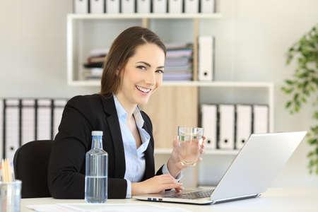 Trabajador de la oficina feliz que sostiene un vaso de agua y una botella mirando a la cámara Foto de archivo - 102076940