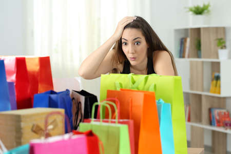 Surprised woman looking at multiple purchases in colorful shopping bags at home