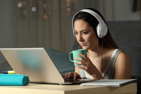 Student watching video tutorials holding a mug late hours in the night at home
