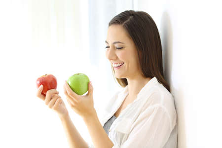 Smiley girl holding two red and green apples leaning on a wall at home