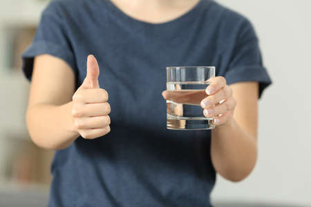 Close up of a woman hands holding a water glass with thumbs up