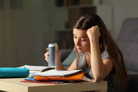 Student preparing exam memorizing notes holding and energy drink in the night at home