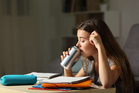 Studious teen studying drinking energy beverage while is studying in the night at home