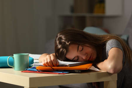 Exhausted student sleeping over homework late night at home