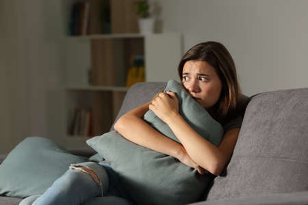 Scared teen at home embracing pillow sitting on a couch in the living room at home Stok Fotoğraf