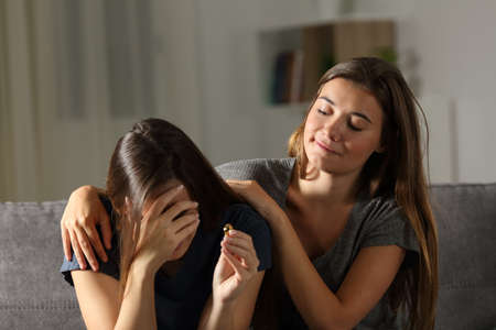 Bad woman is glad about the breakup of a friend sitting on a couch in the living room at home