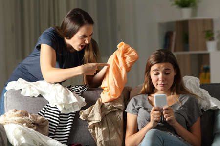 Angry woman scolding to her messy roommate sitting on a couch in the living room at home Stock Photo - 102077241