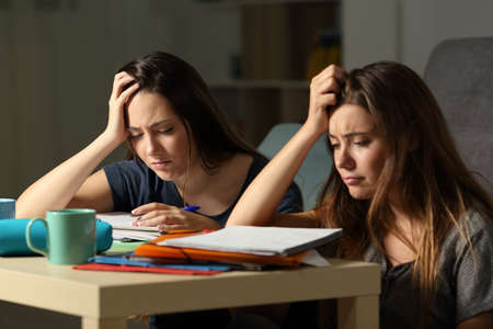 Frustrated students studying hard late hours in the night at home Banco de Imagens