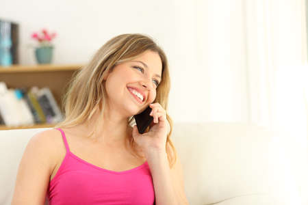 Candid girl talking during a phone call sitting on a couch in the living room at home