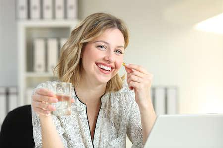 Szczęśliwy pracownik biurowy przedstawiający pigułkę suplementu witaminowego i szklankę wody patrząc na kamery