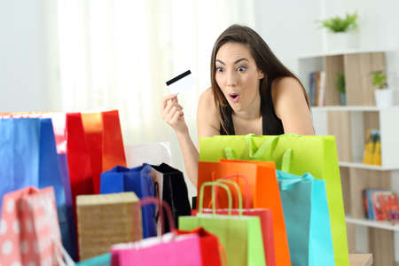 Amazed shopper looking at multiple purchases in colorful shopping bags at home