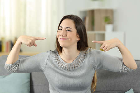 Retrato de vista frontal de una mujer orgullosa apuntando a sí misma sentada en un sofá en la sala de estar en casa