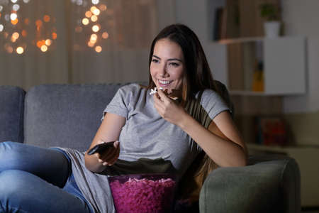 Happy woman watching tv in the night sitting on a couch in the living room at home