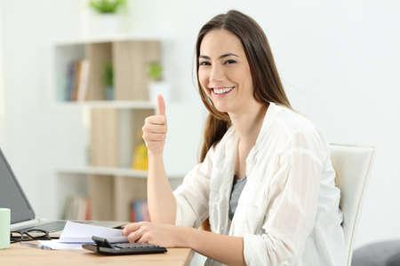 Gelukkige vrouw doet acoounting op zoek naar jou thuis Stockfoto