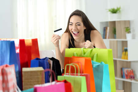Excited shopper looking at multiple purchases in colorful shopping bags at home Foto de archivo - 102851809