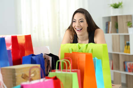 Crazy shopaholic shopper looking at several colorful shopping bags at home