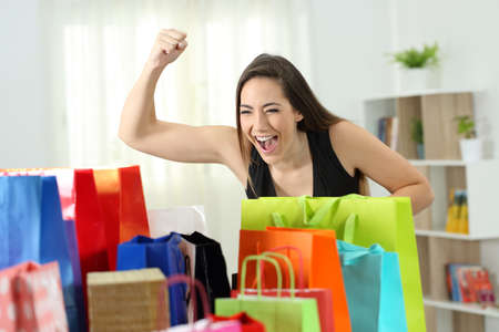 Excited woman looking at multiple colorful shopping bags at home