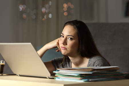 Frustrated self employed looking at camera working late hours in the night at home Stock Photo