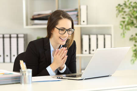 Happy office worker receiving good online news in a laptop  Stockfoto