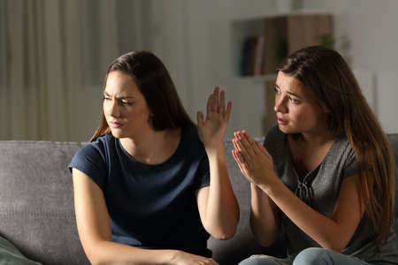Woman begging forgiveness and friend ignoring her sitting on a couch in the living room at home