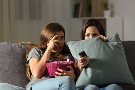 Terrified friends watching tv in the night sitting on a couch in the living room at home Banque d'images - 102851905