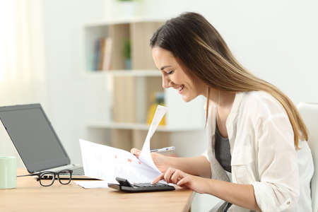 Happy woman doing accounting on a desktop at home Stock Photo