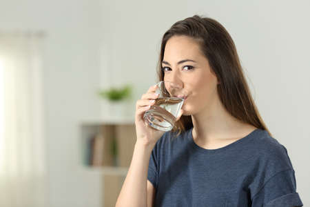 Woman drinking water in a transparent glass and looking at you at home Imagens