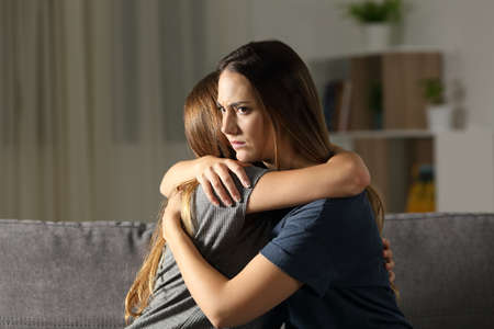 Angry woman hugging a friend sitting on a couch in the living room at home