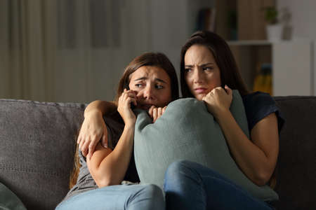 Scared friends at home calling police sitting on a couch in the living room at home Stok Fotoğraf
