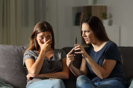 Angry woman scolding her friend about phone content sitting on a couch in the living room at home Stock Photo