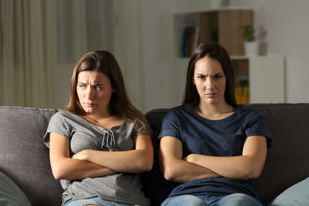 Angry woman looking at camera beside her friend sitting on a couch in the living room at home