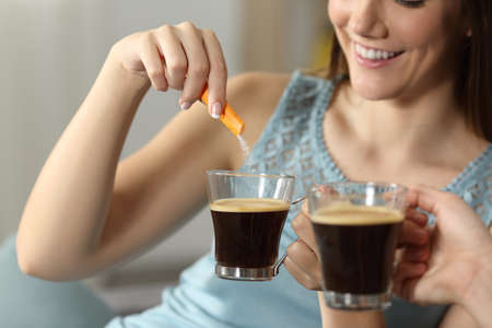 Close up of two women throwing sugar into coffee sitting on a couch in the living room at home Banco de Imagens