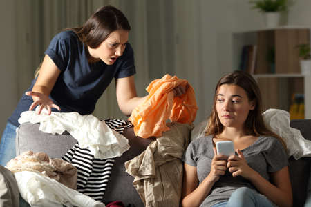 Angry girl scolding her messy roommate sitting on a couch in the living room at home Stockfoto