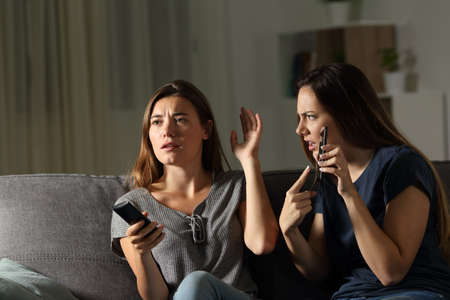 Angry woman showing phone and friend ignoring her sitting on a couch in the living room at home Stock Photo