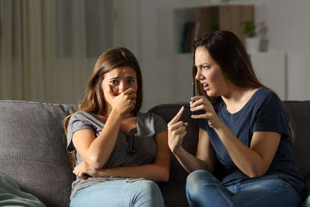 Girl scolding her sad friend about media content sitting on a couch in the living room at home