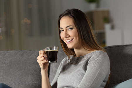 Woman holding coffee cup in the night looking at you sitting on a couch in the living room at home