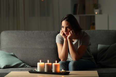 Angry woman boring during a blackout in the night sitting on a couch in the living room at home Stok Fotoğraf