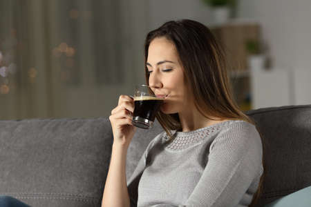 Lady drinking coffee in the night sitting on a couch in the living room at home