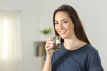 Happy girl holding a transparent glass of water standing at home Foto de archivo - 103246644
