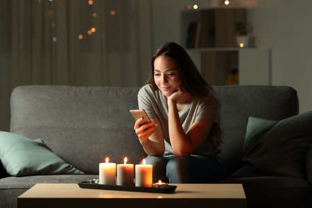 Relaxed girl using phone in the night with candle lights sitting on a couch in the living room at home Stok Fotoğraf