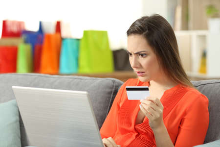 Shocked shopper buying online with credit card sitting on a couch in the living room at home