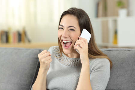 Excited girl receiving good news during a phone call sitting on a couch in the living room at home